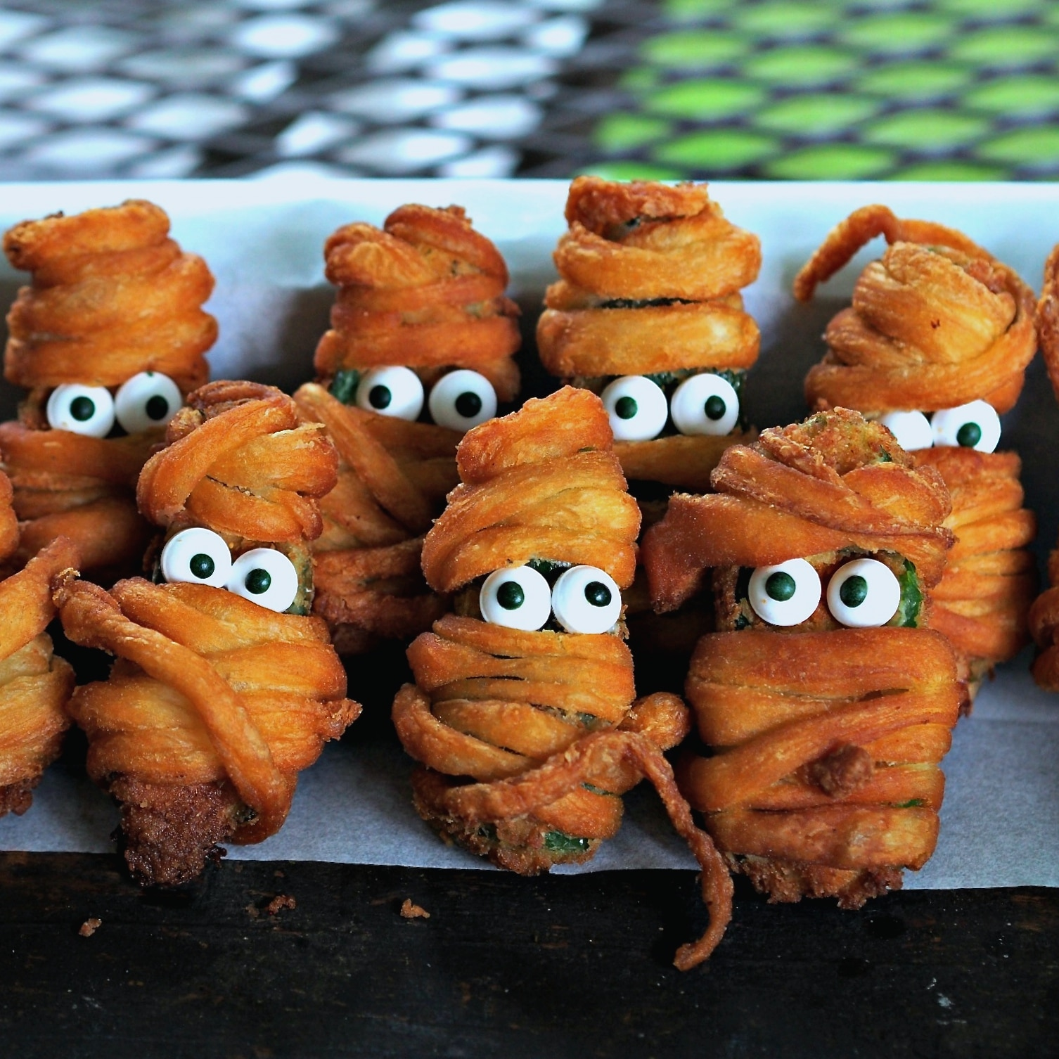 Jalapeno Popper Mummies - a little bit hot, a little bit sweet and a lot of fun. Jalapeno Popper Mummies are the perfect Halloween treat.