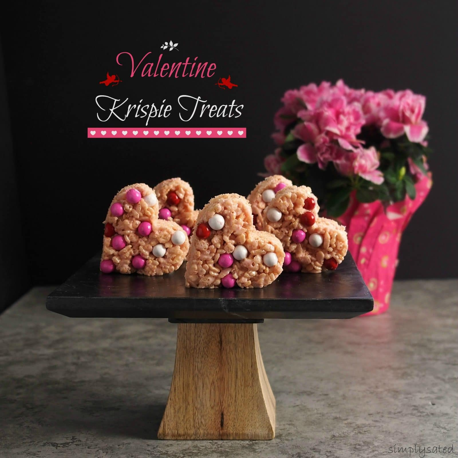 Valentine Krispie Treats made easy using strawberry heart marshmallows, garnished with your favorite candy and cut out with Valentine shaped cookie cutters. Simply Sated