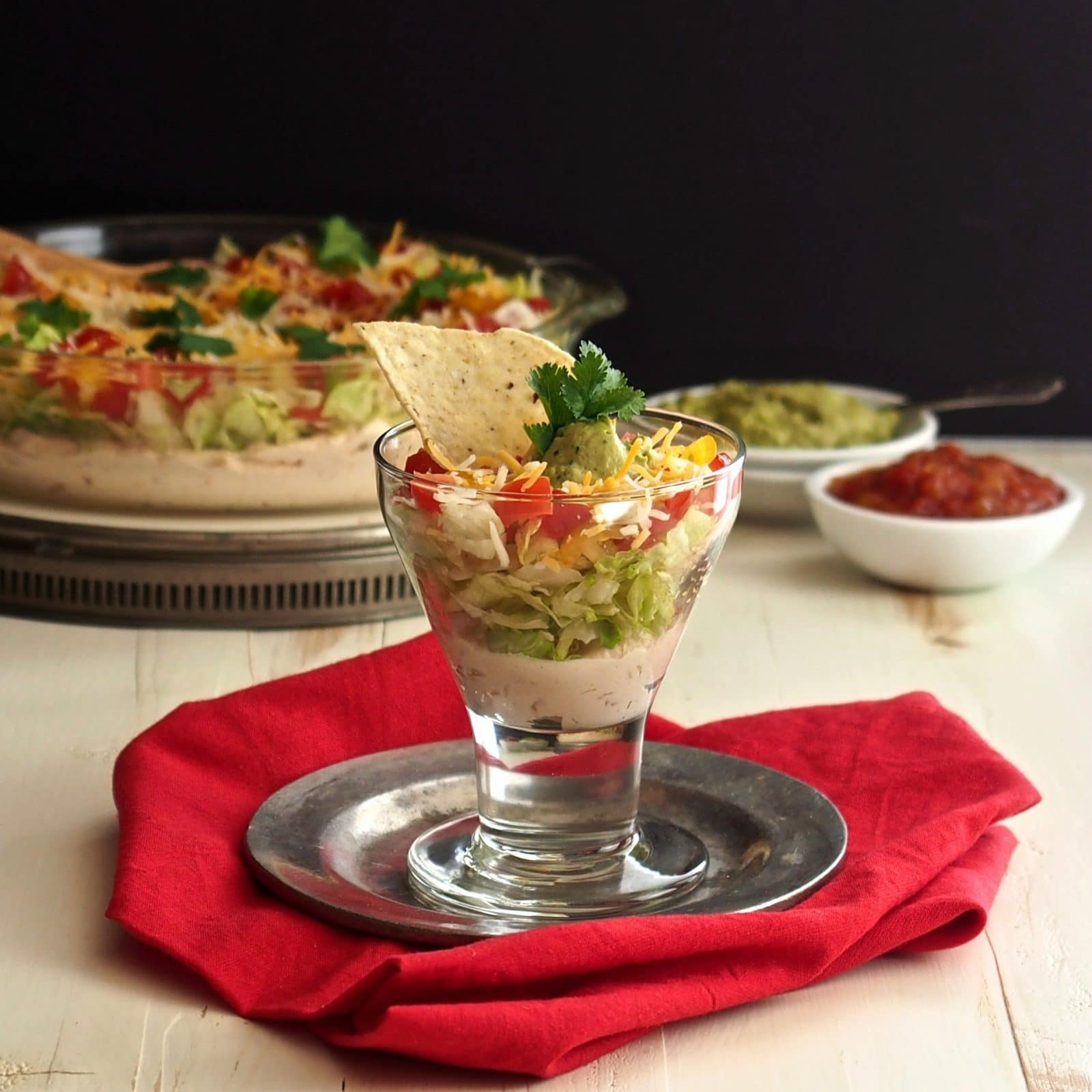 Layered Mexican Dip is as cozy as a patchwork quilt. It is an all-time favorite in its simplest form. Cream cheese, salsa, cheese, lettuce & tomatoes. Simply Sated