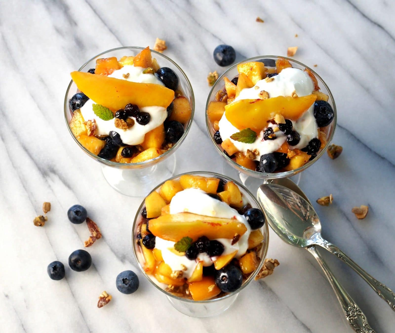 Blueberry Peach Yogurt Parfaits - the perfect healthy breakfast or dessert. Fresh fruit, Greek yogurt, Maple Granola - smooth, naturally sweet & crunchy. Simply Sated