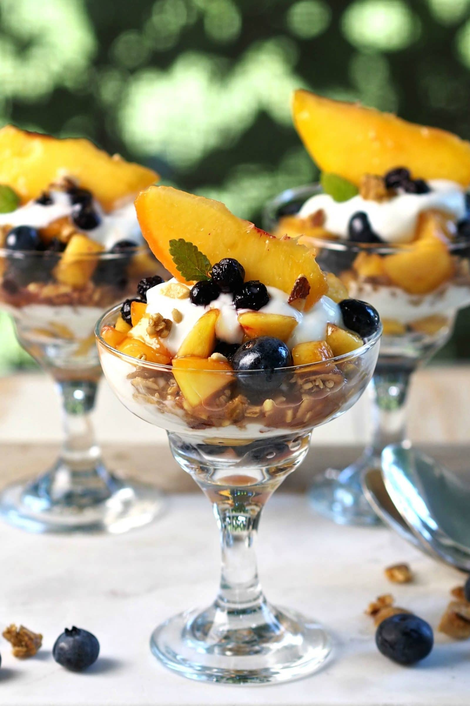 Blueberry Peach Yogurt Parfaits - the perfect healthy breakfast or dessert. Fresh fruit, Greek yogurt, Maple Granola - smooth, naturally sweet & crunchy. Simply Sated