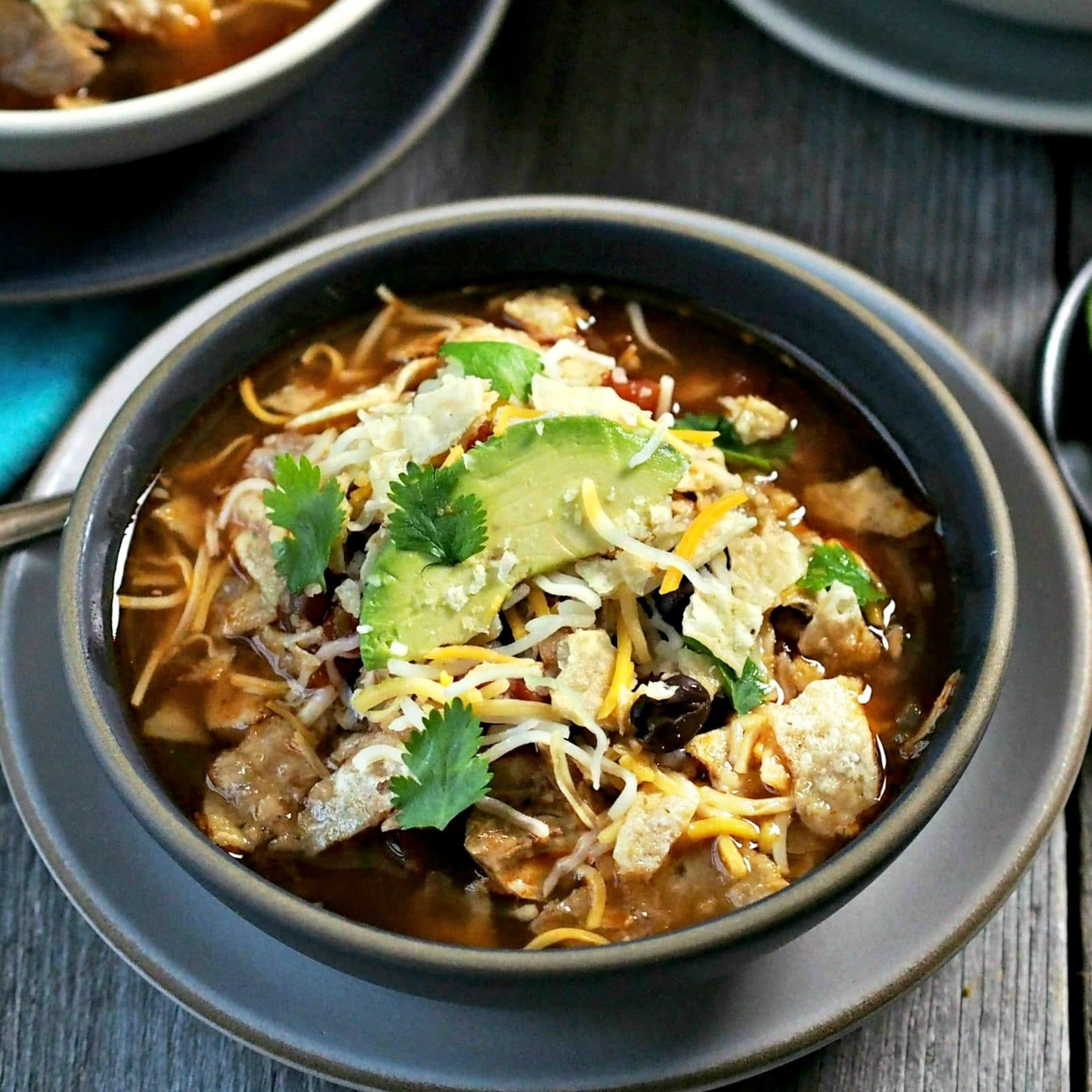 Chicken Tortilla Soup - chicken, beans, tomatoes and Mexican spices simmered together and topped with tortilla chips, cheese & sour cream. So delicious! Simply Sated
