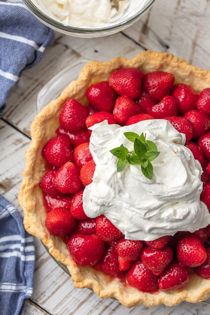 Fresh Strawberry Pie - a mound of glazed, fresh strawberries nestled in a crispy tender crust & topped with whipped cream. As beautiful as it is delicious. Simply Sated